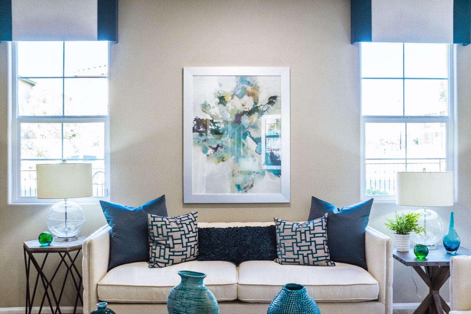 fotografía de una comedor dónde se ve una sillón en el centro beige, y por detrás una ventana en cada lado por dónde entra una luz que inunda el comedor